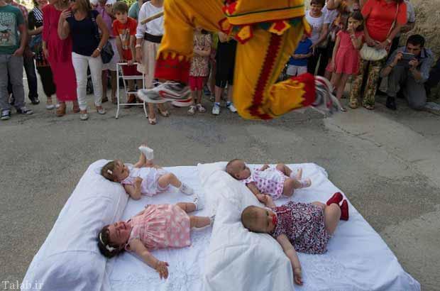 مسابقه عجیب پرش از روی نوزادان در اسپانیا + عکس